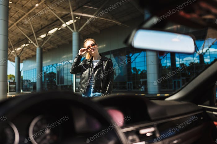 Portrait of pretty smiling girl through windshield of black cabr