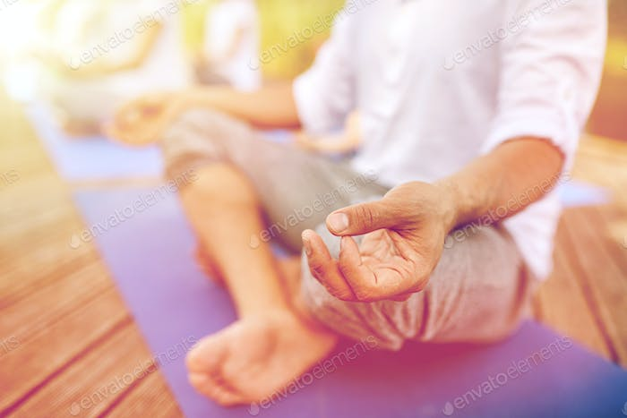 close up of people making yoga exercises outdoors