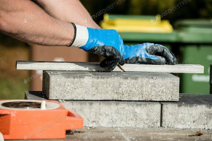 Baumeister markiert einen Pflasterstein oder Block zum Schneiden
