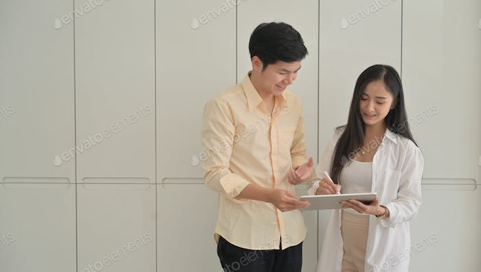 Young teenage students are using tablet to find information on making projects for presentations.