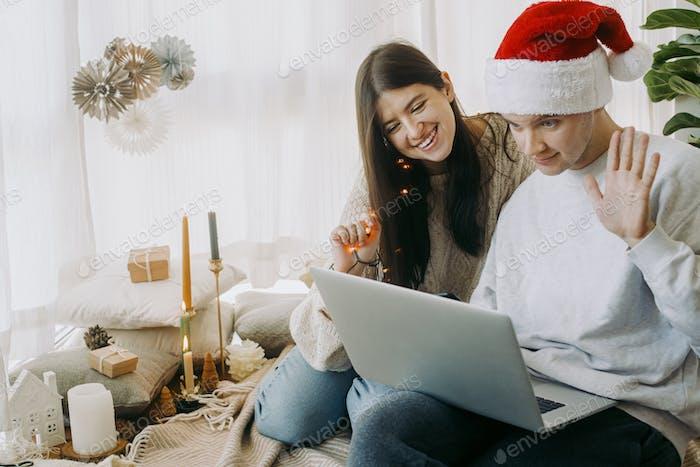 Família jovem feliz acenando as mãos em chamada de vídeo no laptop, comemorando feriados com a família on-line