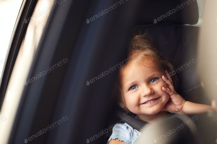 Portrait Of Young Girl Sitting In Child Safety Seat On Car Journey Looking Out Of Window