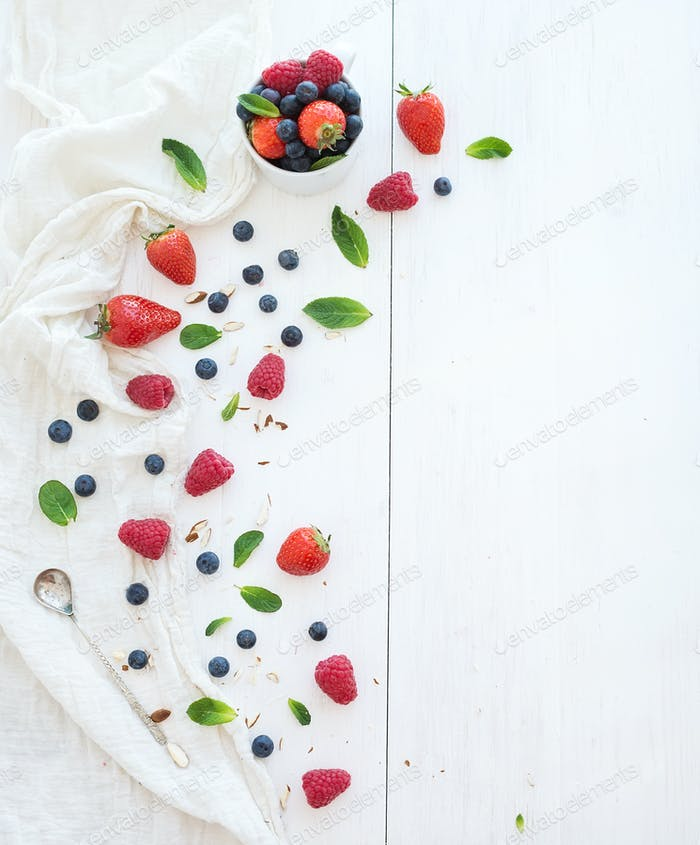 Berry frame with copy space on right. Strawberries, raspberries, blueberries and mint leaves