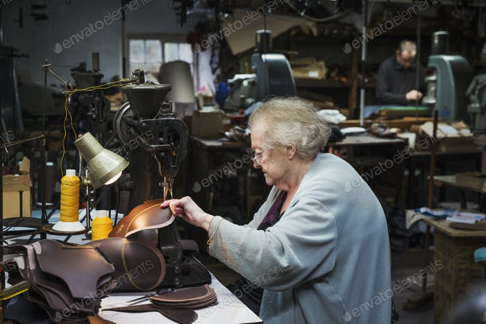 A grey haired senior worker, a woman sitting at a sewing machine in a shoemaker's workshop.