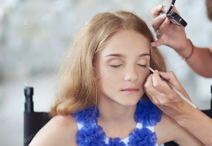 Stylist doing the make-up for a beautiful little girl model.