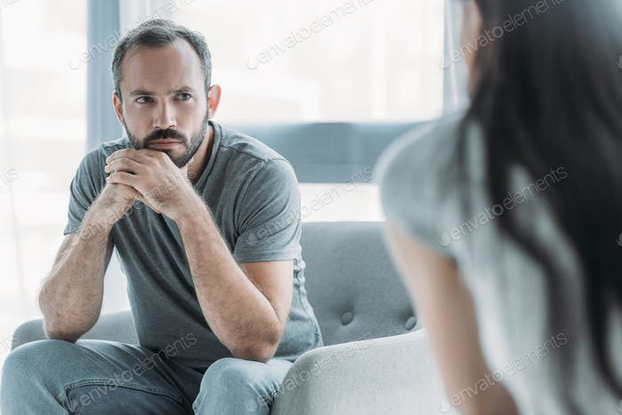 cropped shot of unhappy middle aged man looking at young girlfriend, relationship difficulties
