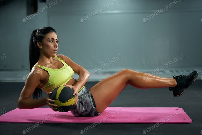 Woman training abs with ball on mat