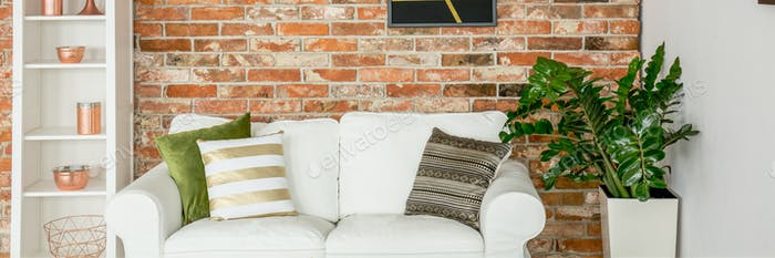 Sofá contra la pared de ladrillo