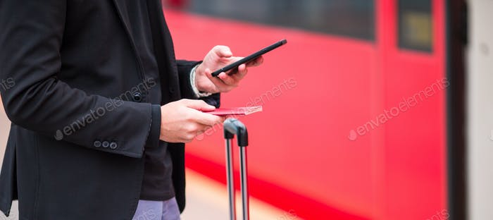 Closeup smartphone in male hands inside in station. Casual young businessman wearing suit jacket