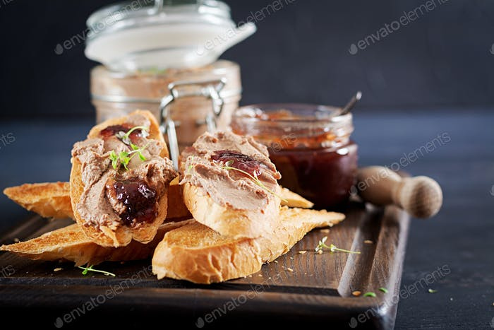 Chicken homemade liver paste or pate in glass jar with toasts and lingonberry jam with chili.