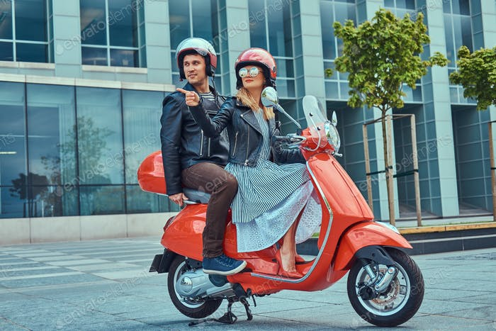 Attractive couple, a handsome man and sexy female riding together on a red retro scooter in a city.