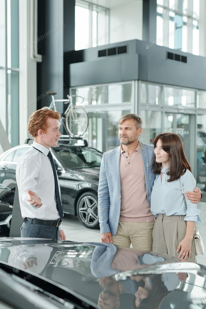 Confident young sales manager in formalwear showing one of new cars to clients