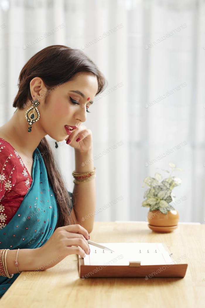 Indian woman checking planner
