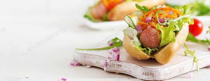Hot Dog mit Gurke, Karotte, Tomaten und Salat auf Holzbac