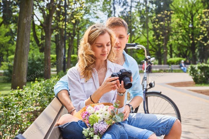 A couple using a compact SLR photo camera.