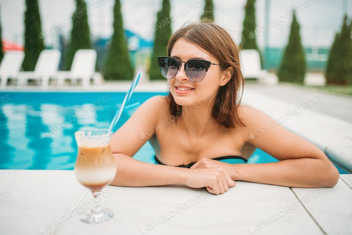 Young girl with cocktail near the swimming pool