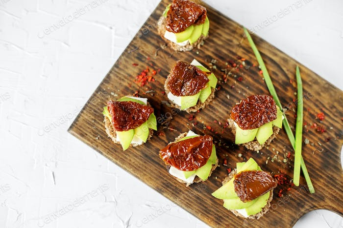 Sandwiches with cheese, avocado and dried tomatoes on the board. Concept for food, healthy food and