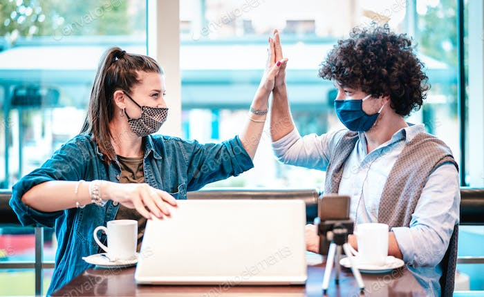 Young milenial influencers at coworking space with facemask