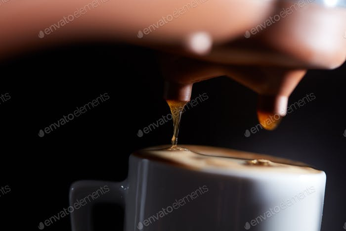 Making fragrant morning coffee in the coffee machine. Macro photo