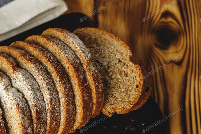 Sliced loaf of bread on wooden board