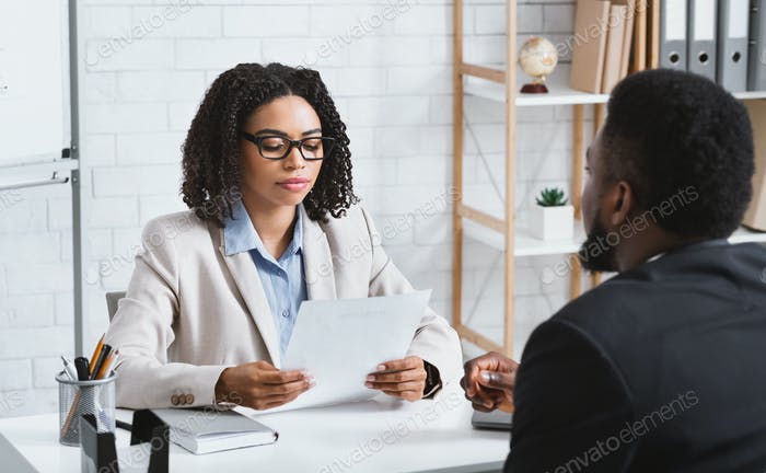 Focused female HR manager studying vacancy applicant's CV during employment interview at office