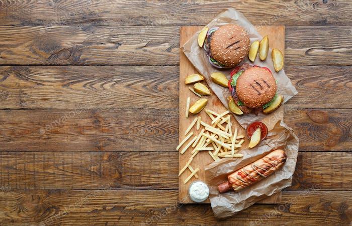 Fast food top view on wood. Hamburger, hotdog and fries