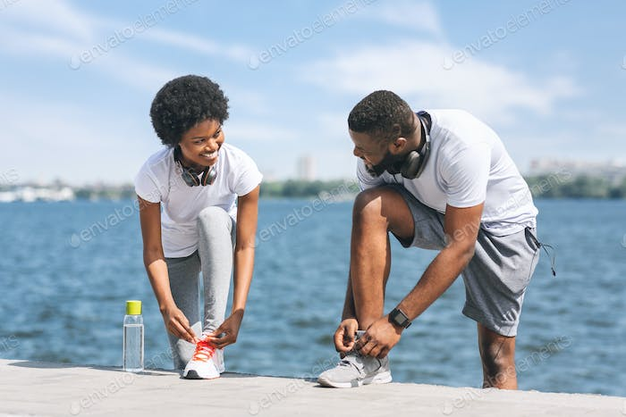 Afro Couple Lacing Shoes Preparing For Morning Jog Outside