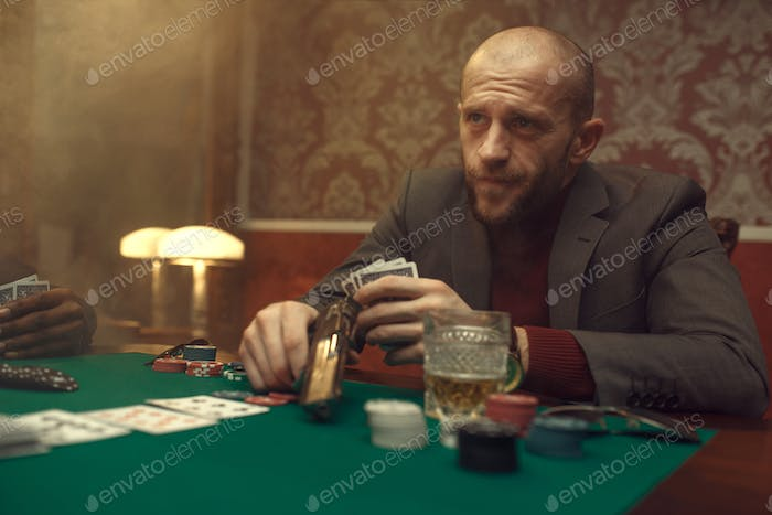 Poker player with gun plays in casino, risk
