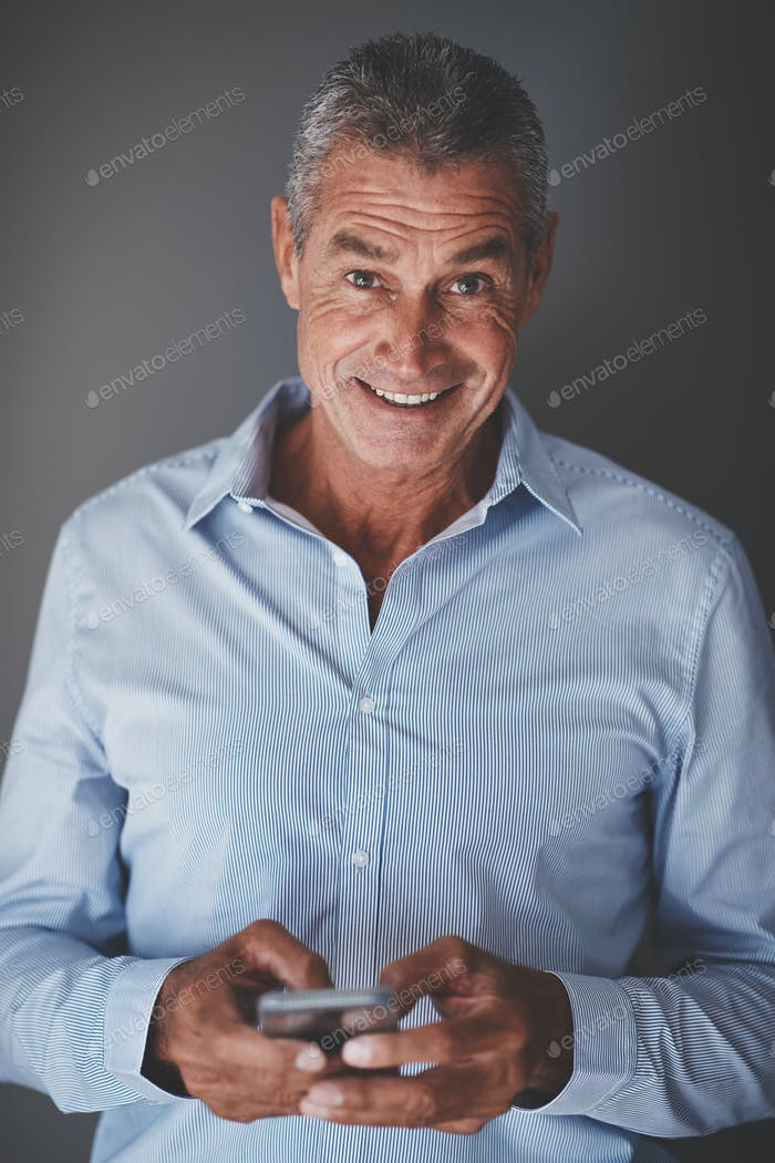 Smiling mature businessman reading text messages against a gray background