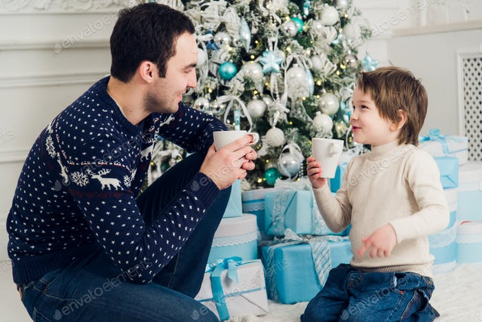 Happy dad and son with cups of tea talking near Christmas time at home