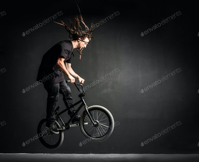 Young sportsman doing stunts on his professional bicycle.
