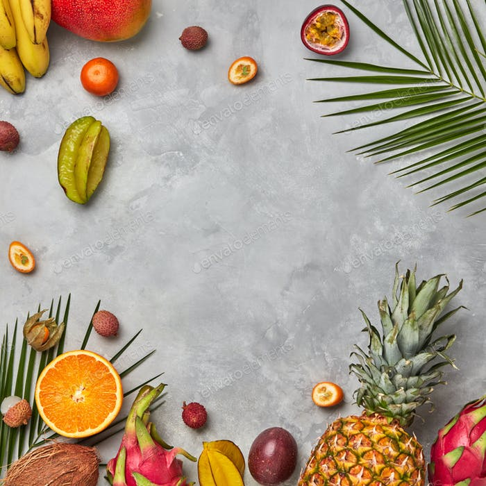 Bright composition of different exotic fruits and palm green leaves on a gray concrete background