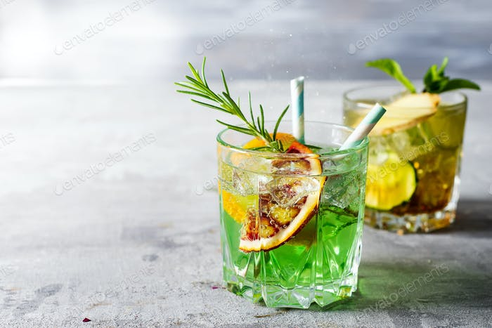 Sweet refreshing mint liqueur, with ice, red mandarin and rosemary on gray concrete stone table