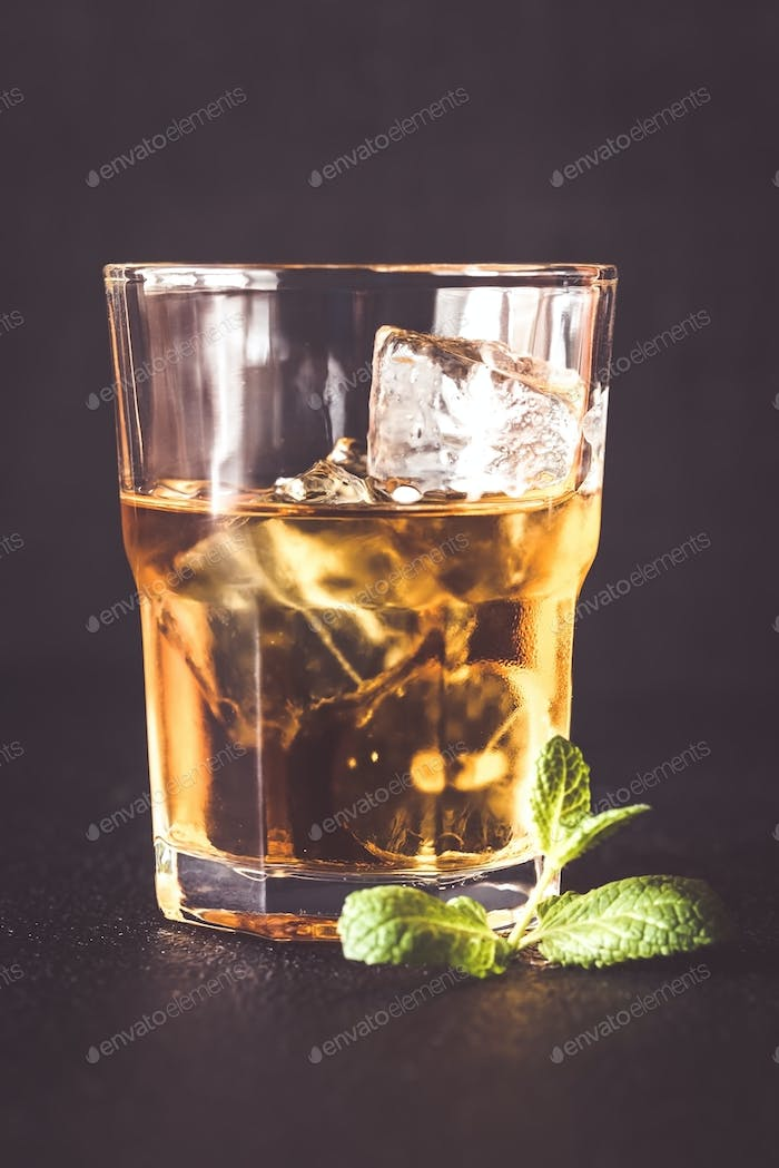 Glass of rum on the dark background