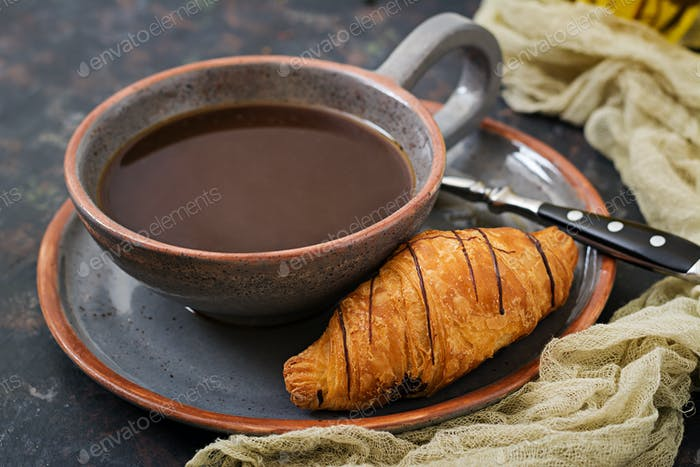 Cup of fragrant coffee and a croissant. Morning breakfast