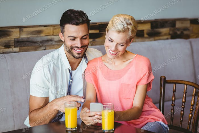 Couple taking a glass of juice at the cafe