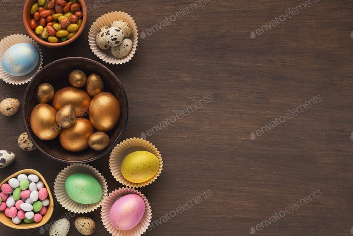 Colorful easter eggs and sprinkles on wooden background