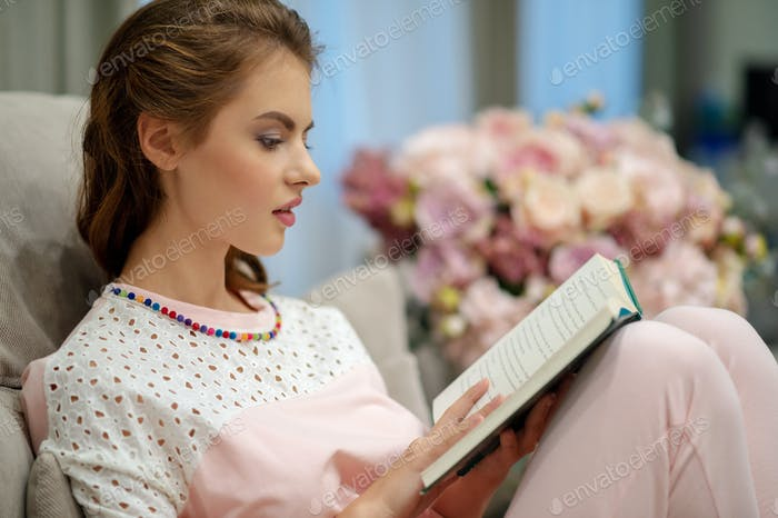 Young attractive woman sitting on the sofa  reading a book enjoy