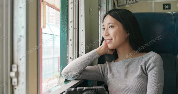 Woman looking out of the window and taking train