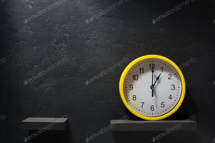 wall clock at shelf on black background