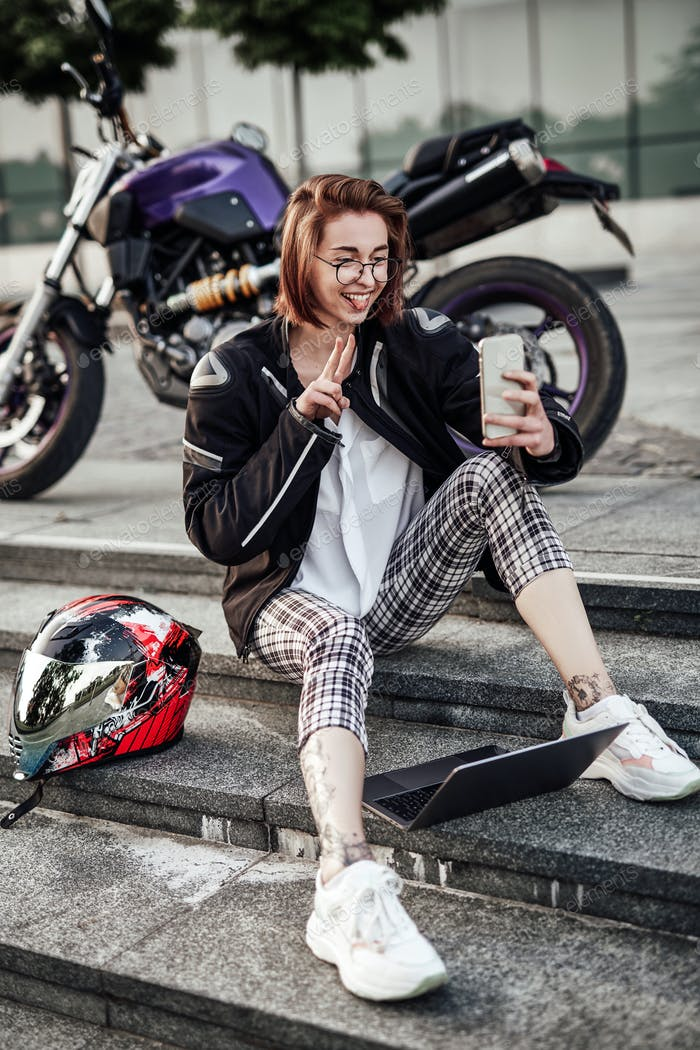 Funny girl sits near her motorcycle and looks at the screen of her phone