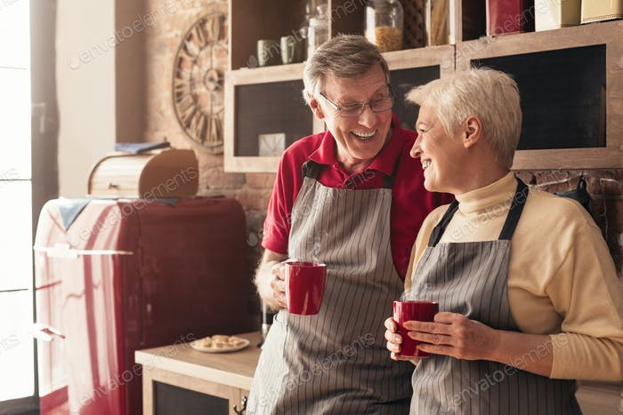 Senior man and woman having nice morning talk with coffee in kitchen