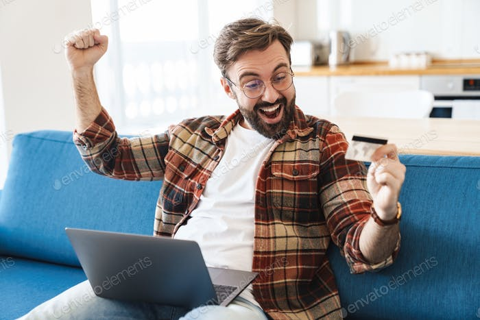 Portrait of happy man using laptop and credit card on sofa at home