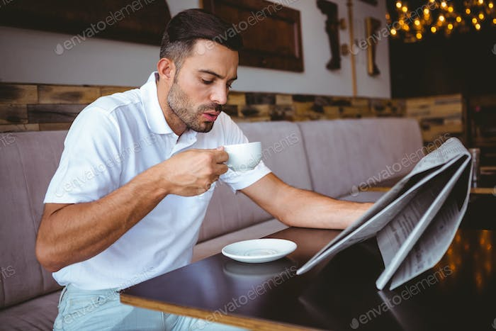 Young man drinking cup of coffee reading newspaper at the cafe