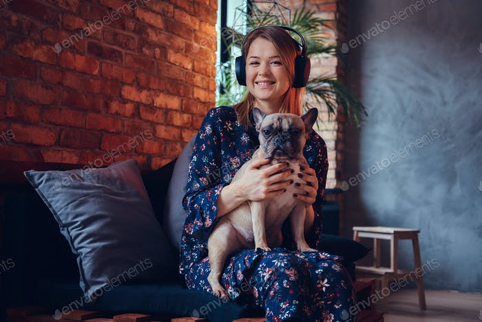 Happy woman sitting with a cute pug in a room with loft interior