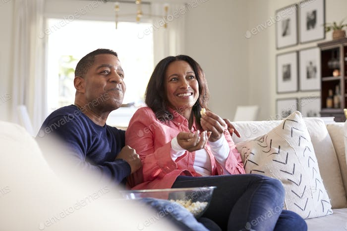 Close up of middle aged couple sitting on the sofa in their living room watching TV