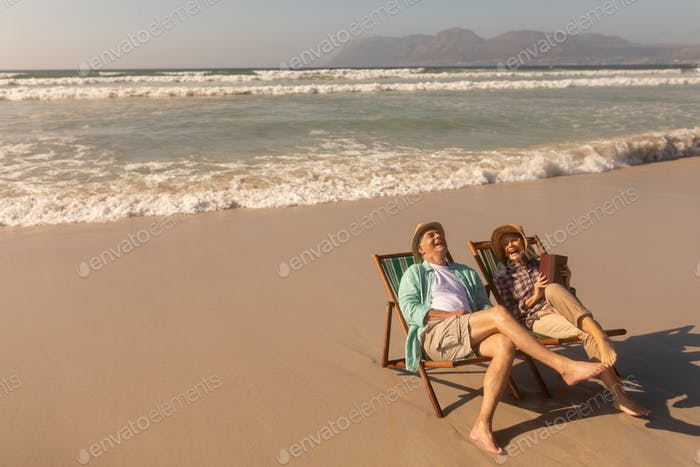 Side view of active senior couple having fun while relaxing on sun lounger at beach