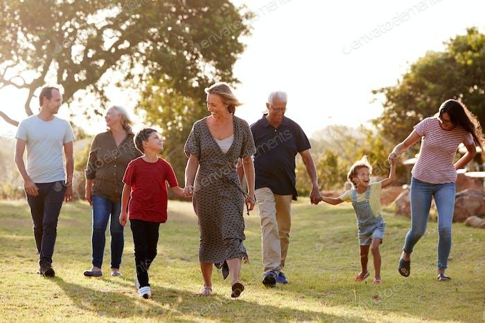 Mehrgeneration Familie Wandern auf dem Land gegen abfackernde Sonne