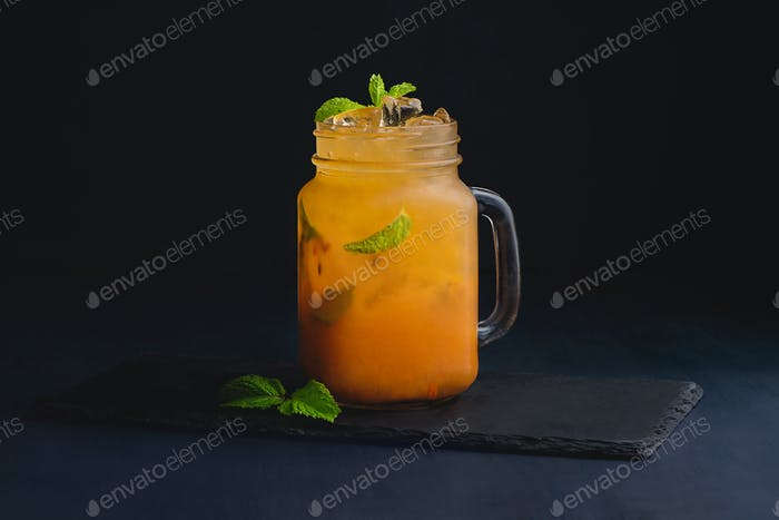 Ice cold citrus cocktail in a vintage glass mason jar. Dark background with copy space for a menu