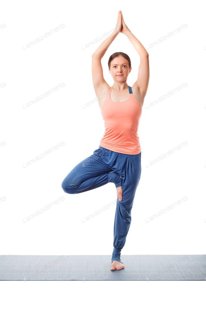 Frau praktiziert Yoga Asana Vrikshasana Baum po